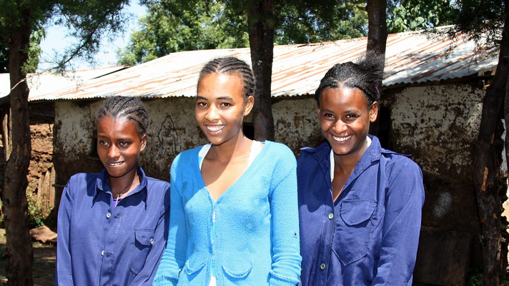 Ihre Zukunft hängt von Bildung ab: Gente Tulu (rechts) und zwei ihrer Mitschülerinnen tragen gerne die blaue Schuluniform. Foto: Kläne