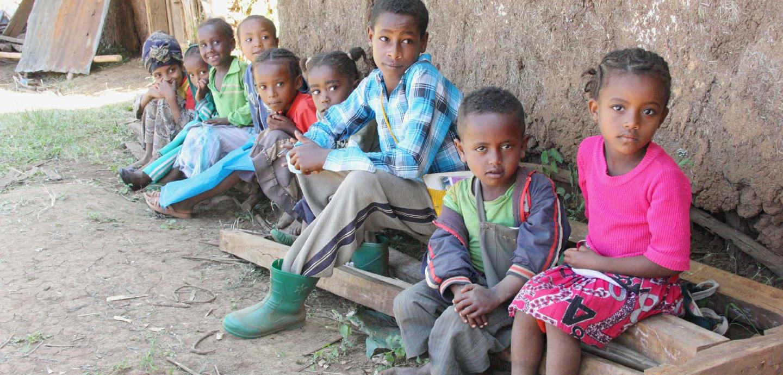 Pause in Kelecha Jibat: Jungen und Mädchen sitzen vor den Klassenzimmern, die zusehends zerfallen. Foto: Kläne